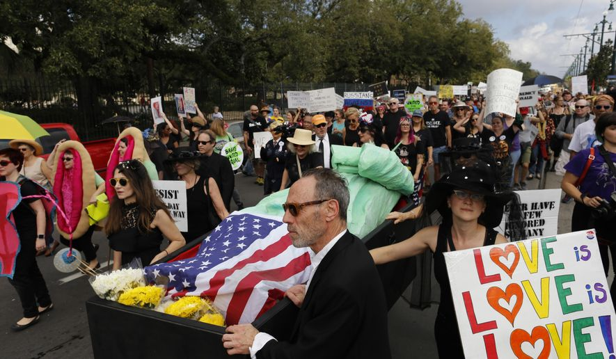 Protesters walk beside The Statue of Liberty in a coffin during a mock second line jazz funeral procession down the streets of New Orleans in protest of the inauguration of Donald Trump Friday, Jan. 20, 2017. (AP Photo/Max Becherer)