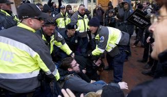 Police try to remove demonstrators from attempting to block people entering a security checkpoint, Friday, Jan. 20, 2017, ahead of President-elect Donald Trump's inauguration in Washington. ( AP Photo/Jose Luis Magana)