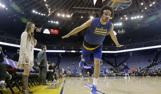 In this Jan. 12, 2017 photo, Golden State Warriors forward Anderson Varejao, right, demonstrates a yoga position while posing for photographs as yoga instructor and Warriors director of corporate communications Lisa Goodwin watches before an NBA basketball game between the Warriors and the Detroit Pistons in Oakland, Calif. Warriors head coach Steve Kerr gave Golden State a day off from the practice floor one day last week so they could practice yoga instead. (AP Photo/Jeff Chiu)