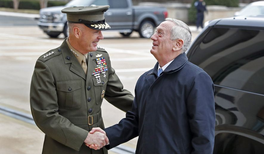 Chairman of the Joint Chiefs Gen. Joseph Dunford, left, shakes hands with Secretary of Defense James Mattis as Mattis looks up at the Pentagon upon his arrival, Saturday, Jan. 21, 2017 in Washington. (AP Photo/Alex Brandon)