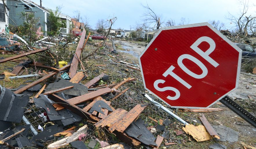 A bent stop sign stands on the corner of Cedar and Chestnut Streets in Hattiesburg, Miss., after a tornado struck the city on Saturday, Jan. 21, 2017. (Susan Broadbridge/Hattiesburg American via AP)