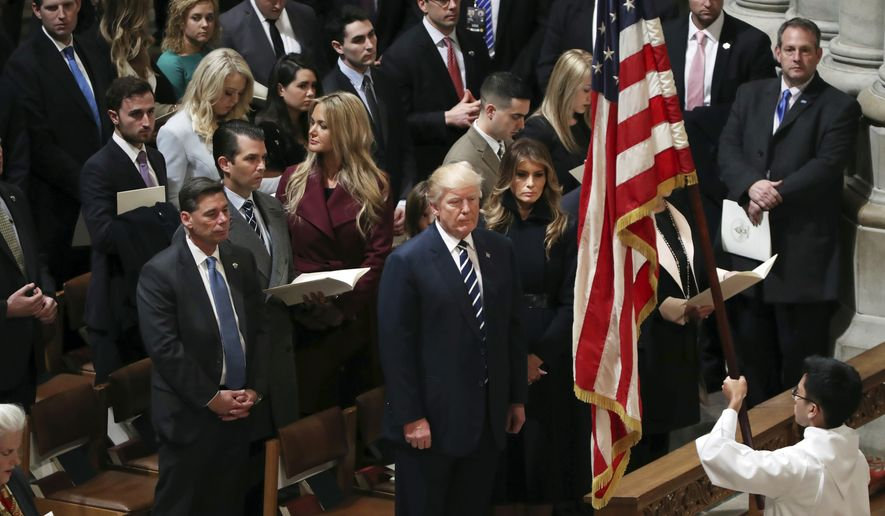 President Donald Trump, center, with first lady Melania Trump, and his family, watch an altar boy carry the American flag during a National Prayer Service at the National Cathedral, in Washington, Saturday, Jan. 21, 2017. (AP Photo/Manuel Balce Ceneta)