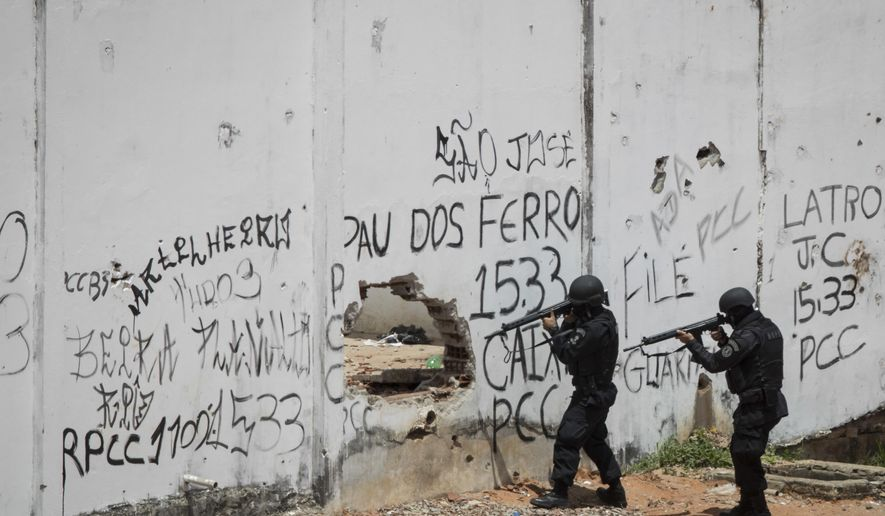 Special Operations Battalion Police officers enter the Alcacuz prison amid tension between rival gangs in Nisia Floresta, near Natal, Brazil, Saturday, Jan. 21, 2017.Military police took control of the prison in northeastern Brazil after fighting between rival gangs left 26 inmates dead, the latest in a spate of violence in the country's penitentiaries. (AP Photo/Felipe Dana)
