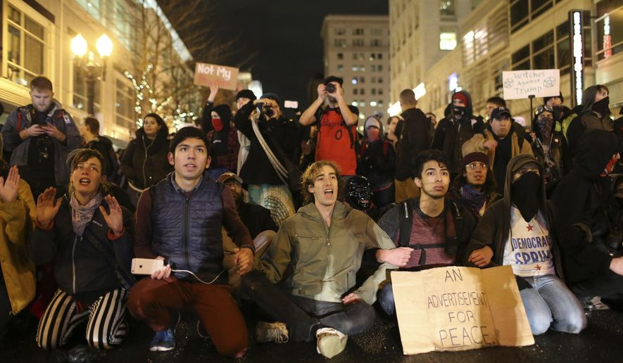 "A crowd marches in protest through the streets of Portland, Ore., following Donald Trump's presidential inauguration, Friday, Jan. 20, 2017. Police in Portland used incendiary devices and tear gas to disperse a crowd of people protesting President Trump. Authorities said some people in the crowd - that at one point numbered in the thousands - threw rocks, bottles, flares and ""unknown liquid"" at officers Friday night.  (Stephanie Yao Long/The Oregonian via AP)"