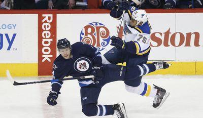 St. Louis Blues' Ryan Reaves (75) and Winnipeg Jets' Paul Postma (4) collide  during first period of an NHL hockey game in Winnipeg, Manitoba, Saturday, Jan. 21, 2017. (John Woods/The Canadian Press via AP)