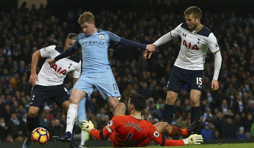Manchester City's Kevin De Bruyne, left shoots past a diving Tottenham Hotspur's goalkeeper Hugo Lloris to score his sides second goal of the game during the English Premier League soccer match between Manchester City and Tottenham Hotspur at the Etihad stadium in Manchester, England, Saturday, Jan., 21, 2017. (AP Photo/Dave Thompson)