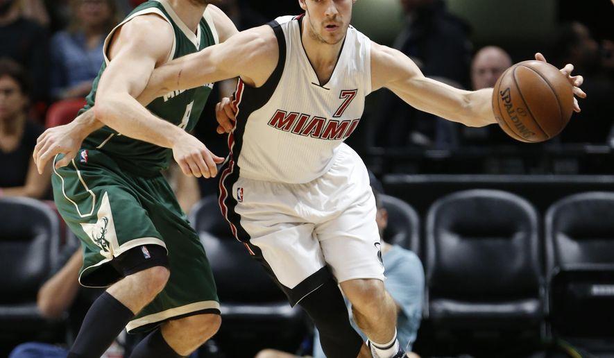 Miami Heat guard Goran Dragic (7) drives around Milwaukee Bucks guard Matthew Dellavedova during the first half of an NBA basketball game, Saturday, Jan. 21, 2017, in Miami. (AP Photo/Wilfredo Lee)