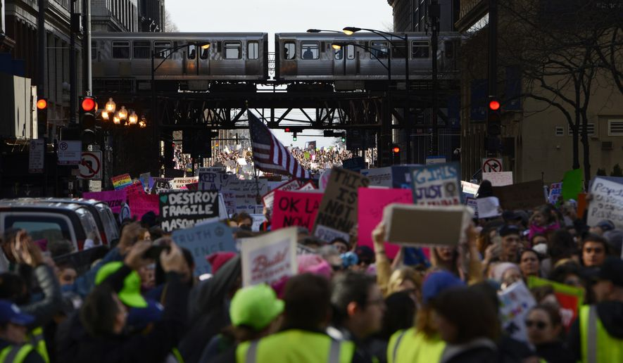 Protesters protest newly inaugurated President Donald Trump during a women's march Saturday, Jan. 21, 2017, in Chicago. (AP Photo/Paul Beaty)