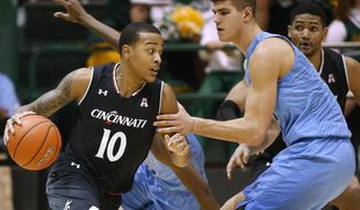 Cincinnati guard Troy Caupain (10) drives against Tulane center Ryan Smith, right, during the first half of an NCAA college basketball game Saturday, Jan. 21, 2017, in New Orleans. (AP Photo/Jonathan Bachman)