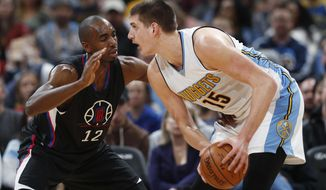 Los Angeles Clippers forward Luc Mbah a Moute, left, of Cameroon, defends again Denver Nuggets forward Nikola Jokic, of Serbia, as he looks to shoot the ball in the first half of an NBA basketball game Saturday, Jan. 21, 2017, in Denver. (AP Photo/David Zalubowski)