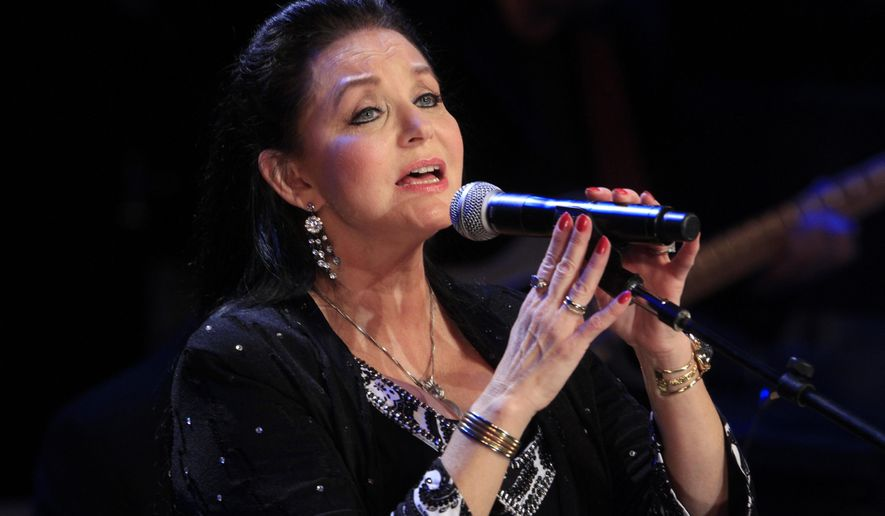 FILE - In this Oct. 21, 2012 file photo, Crystal Gayle performs at the Country Music Hall of Fame Inductions in Nashville, Tenn. Country music legend Gayle is being inducted into the Grand Ole Opry in Nashville, nearly a half-century after she first walked onto its stage to perform as a teenager. Gayle's sister, country luminary Loretta Lynn, will induct her into the country music institution during a Saturday night, Jan. 21, 2017, ceremony at the Ryman Auditorium, the Grand Ole Opry announced. (Photo by Wade Payne/Invision/AP, File)