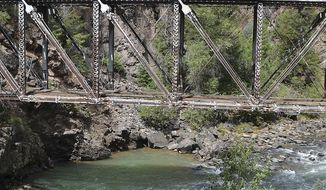 ADVANCE FOR USE SATURDAY, JAN. 21 - FILE - In this Aug. 16, 2013, file photo, the Galloping Goose, a restored rail bus, crosses a high trestle bridge across the Animas River on a trip to Cascade Canyon from Durango, Colo. Managers of the Galloping Goose have partnered with the Durango-Silverton Narrow Gauge Railroad to make the run from Durango to Cascade Canyon for the first time in the winter in 60 years. The trip will be made on February 18 and 19. (Sam Green//The Journal via AP, File)