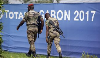 Soldiers patrol during Gabon's soccer team training session at the Stade de l'Amitie, Libreville, Gabon, Saturday, Jan. 21, 2017, ahead of their African Cup of Nations Group A soccer match against Cameroon. (AP Photo/Sunday Alamba)