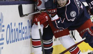 Carolina Hurricanes' Ty Rattie, left, and Columbus Blue Jackets' Scott Harrington chase a loose puck during the first period of an NHL hockey game Saturday, Jan. 21, 2017, in Columbus, Ohio. (AP Photo/Jay LaPrete)