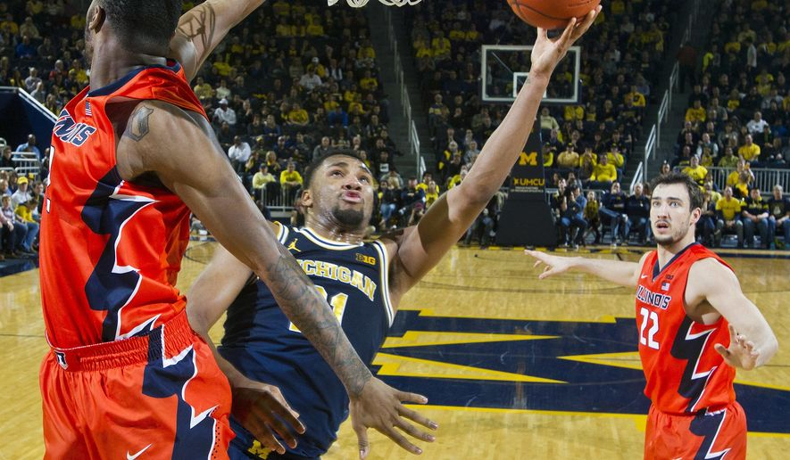 Michigan guard Zak Irvin (21) tries to make a basket, defended by Illinois forward Kipper Nichols, front, in the first half of an NCAA college basketball game at Crisler Center in Ann Arbor, Mich., Saturday, Jan. 21, 2017. (AP Photo/Tony Ding)