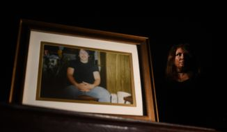 ADVANCE FOR SATURDAY, JAN. 21, 2017 - In this Jan. 10, 2017 photo, Desiree Kalodnicki, who is the sister of of John Patrick Walter, seen in photo at left, reflects on her brother's life at her home in Peyton, Colo. Kalodnicki's brother died in Fremont County jail of severe withdrawal and she has sued the county and the private health care worker over it.  The number of people who died in Colorado's jails more than doubled in four years, following a national trend of a rising death toll among inmates in city and county jails across the country. (RJ Sangosti/The Denver Post via AP)