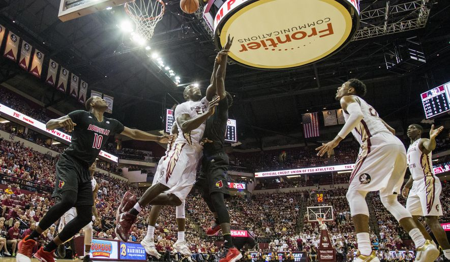 Florida State center Michael Ojo (50) fouls Louisville forward Mangok Mathiang in the first half of an NCAA college basketball game in Tallahassee, Fla., Saturday, Jan. 21, 2017. (AP Photo/Mark Wallheiser)