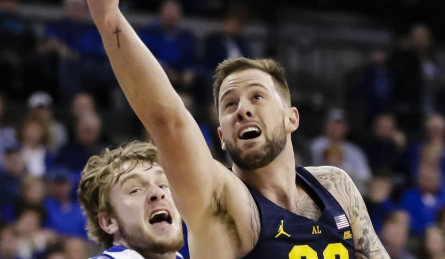 Marquette's Katin Reinhardt (22) goes for a layup past Creighton's Toby Hegner (32) during the first half of an NCAA college basketball game in Omaha, Neb., Saturday, Jan. 21, 2017. (AP Photo/Nati Harnik)