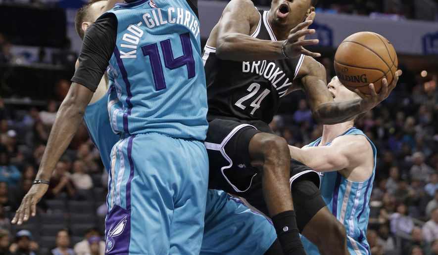Brooklyn Nets' Rondae Hollis-Jefferson (24) tries to shoot over Charlotte Hornets' Michael Kidd-Gilchrist (14) in the first half of an NBA basketball game in Charlotte, N.C., Saturday, Jan. 21, 2017. (AP Photo/Chuck Burton)