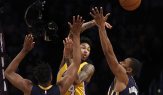 Los Angeles Lakers forward Brandon Ingram, center, passes the ball away from pressure by Indiana Pacers center Myles Turner, left, and guard Glenn Robinson, right, during the first half of an NBA basketball game in Los Angeles, Friday, Jan. 20, 2017. (AP Photo/Alex Gallardo)