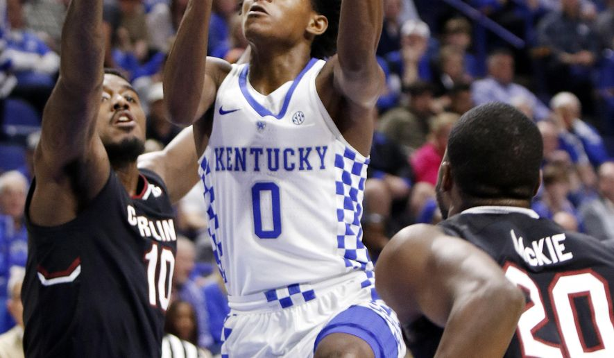 Kentucky's De'Aaron Fox (0) shoots between the defense of South Carolina's Duane Notice (10) and Justin McKie (20) during the first half of an NCAA college basketball game, Saturday, Jan. 21, 2017, in Lexington, Ky. (AP Photo/James Crisp)