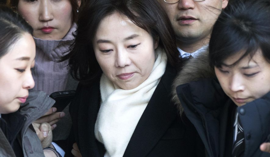 In this Friday, Jan. 20, 2017 photo, South Korean Culture Minister Cho Yoon-sun, center, leaves the Seoul Central District Court in Seoul, South Korea, after attending a hearing. South Korean prosecutors on Saturday, Jan. 21, arrested Cho and President Park Geun-hye's former top presidential adviser over allegations that they blacklisted artists critical of the government. (Choi Jae-koo/Yonhap via AP)