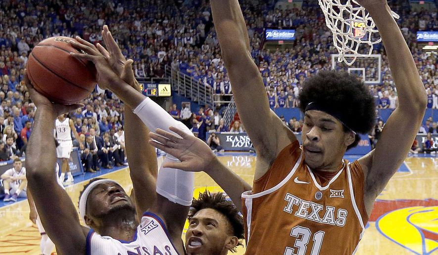 Kansas' Carlton Bragg Jr. (15) shoots under pressure from Texas' James Banks, center, and Jarrett Allen (31) during the first half of an NCAA college basketball game, Saturday, Jan. 21, 2017, in Lawrence, Kan. (AP Photo/Charlie Riedel)