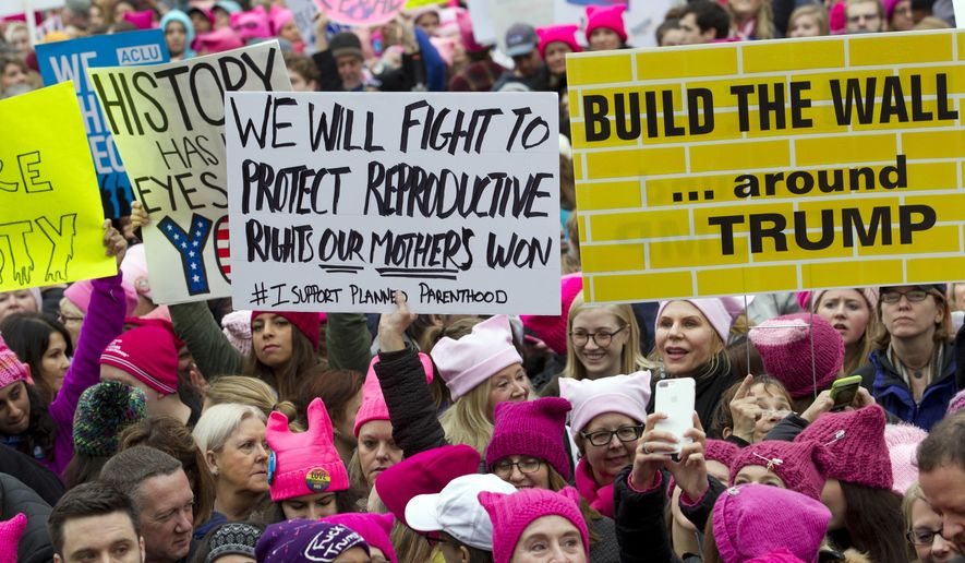 Women with bright pink hats and signs begin to gather early and are set to make their voices heard on the first full day of Donald Trump's presidency, Saturday, Jan. 21, 2017 in Washington.  Organizers of the Women's March on Washington expect more than 200,000 people to attend the gathering.  Other protests are expected in other U.S. cities.  ( AP Photo/Jose Luis Magana)