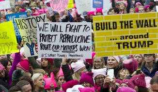 Women with bright pink hats and signs begin to gather early and are set to make their voices heard on the first full day of Donald Trump's presidency, Saturday, Jan. 21, 2017, in Washington. (AP Photo/Jose Luis Magana) ** FILE **