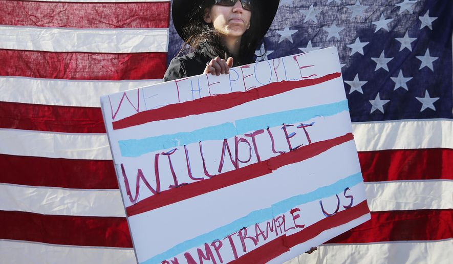 Allison Poff, of Fort Collins, Colo., holds a sign during the Women's March Saturday, Jan. 21, 2017, in downtown Cheyenne, Wyo. Around 1,500 and 2,000 people took park in the march to focus on the rights of women and other minority and disadvantaged groups. (Blaine McCartney  /The Wyoming Tribune Eagle via AP)