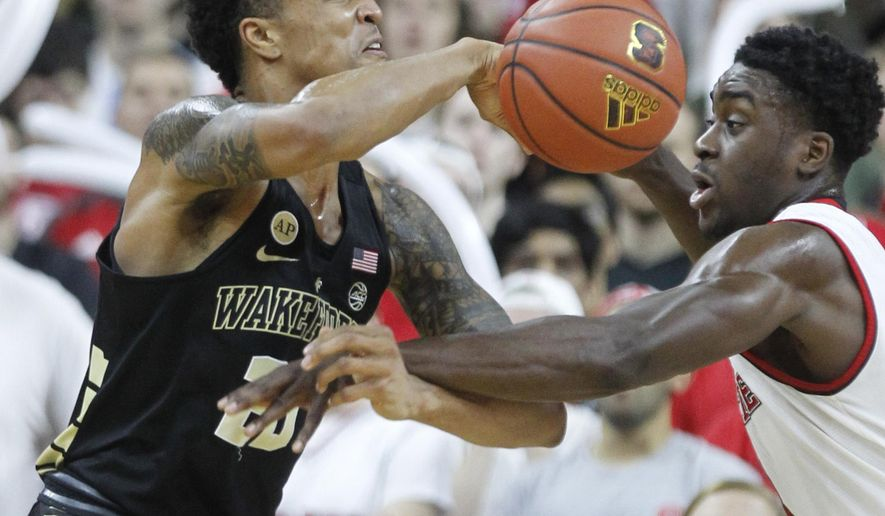 N.C. State's Abdul-Malik Abu (0), right, defends Wake Forest's John Collins (20) during the first half of an NCAA college basketball game at PNC Arena in Raleigh, N.C., Saturday, Jan. 21, 2017. (Ethan Hyman/The News & Observer via AP)