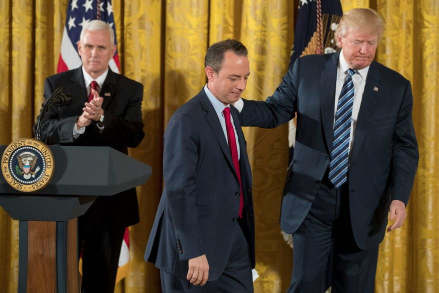 """President Trump leads Chief of Staff Reince Priebus off the stage on Sunday after a swearing-in ceremony for 30 senior staff members. With Vice President Mike Pence (left), he gave a pep talk to """"prove worthy of this moment in history."""" (Associated Press)"""