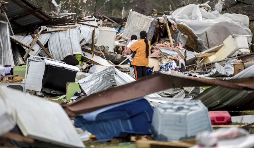 A woman holds a child while walking through a farm that was damaged by a tornado, Sunday, Jan. 22, 2017, in Adel, Ga. (AP Photo/Branden Camp)