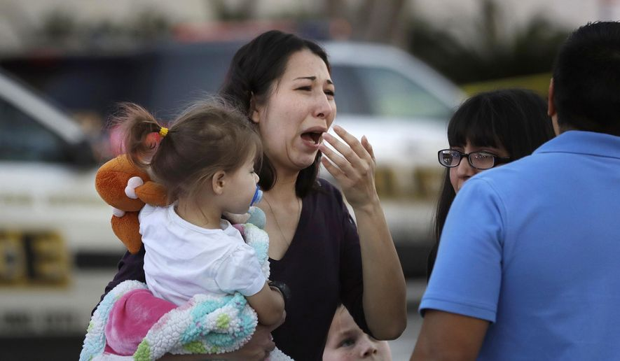 A woman holds her child after San Antonio police helped her and other shoppers exit the Rolling Oaks Mall, Sunday, Jan. 22, 2017, in San Antonio, after a deadly shooting. Authorities say several were injured after a robbery at the shopping mall. (AP Photo/Eric Gay)