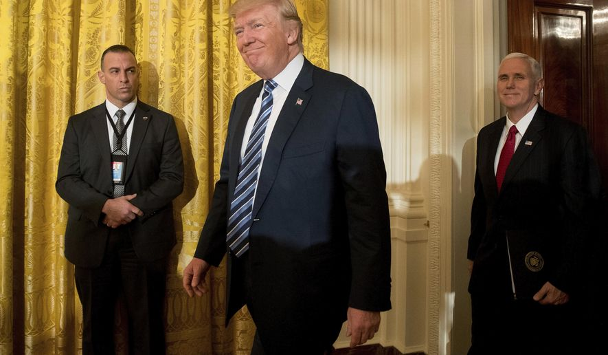 President Donald Trump, center, accompanied by Vice President Mike Pence, right, arrives for a White House senior staff swearing in ceremony in the East Room of the White House, Sunday, Jan. 22, 2017, in Washington. (AP Photo/Andrew Harnik)