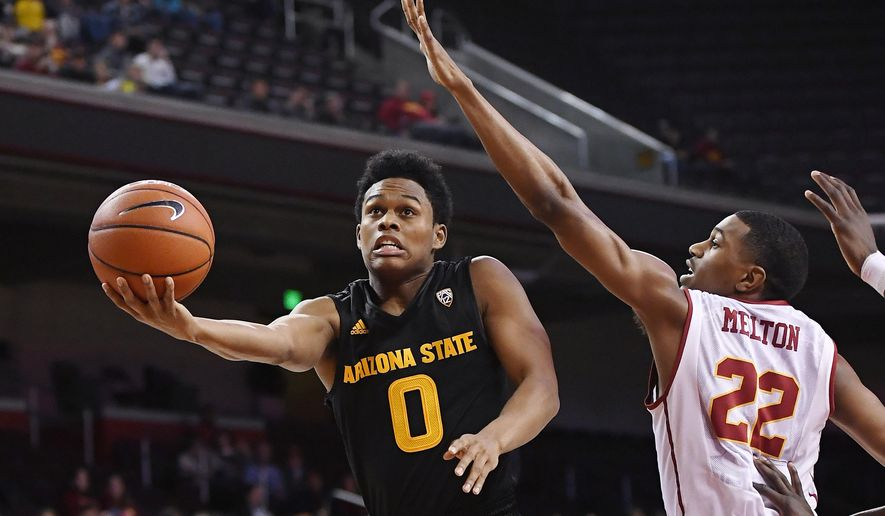 Arizona State guard Tra Holder, left, shoots as Southern California guard De'Anthony Melton defends during the first half of an NCAA college basketball game Sunday, Jan. 22, 2017, in Los Angeles. (AP Photo/Mark J. Terrill)