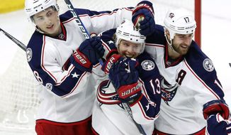 Columbus Blue Jackets' Cam Atkinson (13) celebrates his overtime goal with teammates Brandon Dubinsky (17) and Zach Werenski (8) during NHL hockey action in Ottawa, Ontario, Sunday, Jan. 22, 2017. (Fred Chartrand/The Canadian Press via AP)