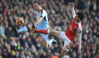 Burnley's Ashley Barnes, left, and Arsenal's Laurent Koscielny battle for the ball during their English Premier League soccer match at The Emirates Stadium, London, Sunday, Jan. 22, 2017. (Mike Egerton/PA via AP)