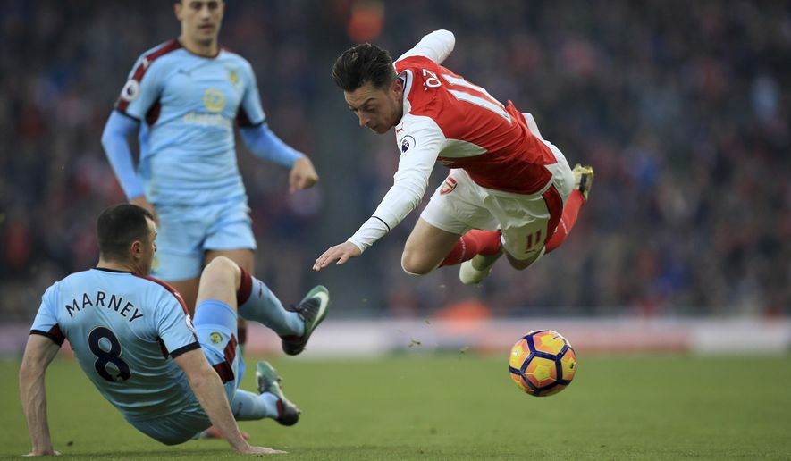 Burnley's Dean Marney, left, and Arsenal's Mesut Ozil battle for the ball during their English Premier League soccer match at The Emirates Stadium, London, Sunday, Jan. 22, 2017. (Mike Egerton/PA via AP)