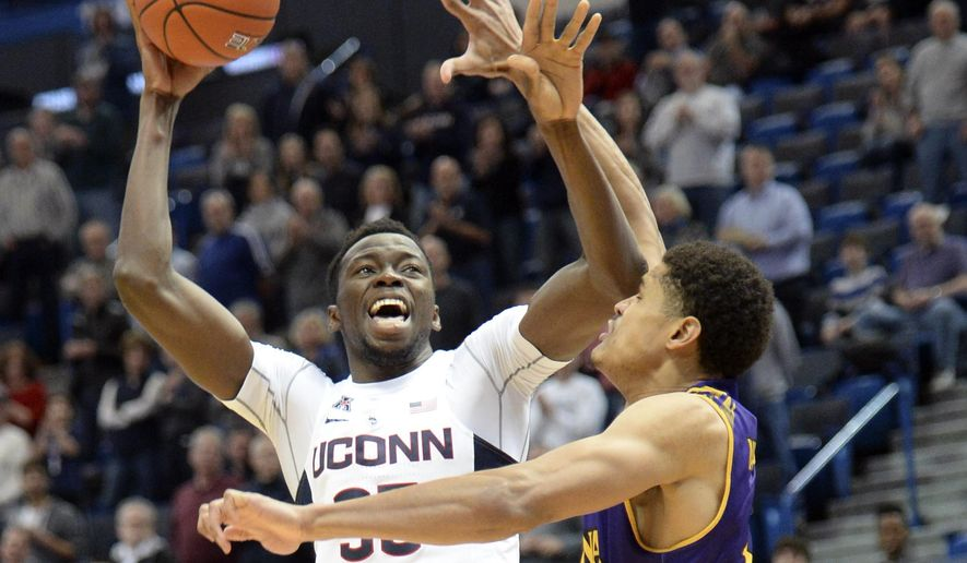 Connecticut's Amida Brimah, left, shoots over East Carolina's Andre Washington (31) during the first half of an NCAA college basketball game Sunday, Jan. 22, 2017, in Hartford, Conn. (AP Photo/Stephen Dunn)