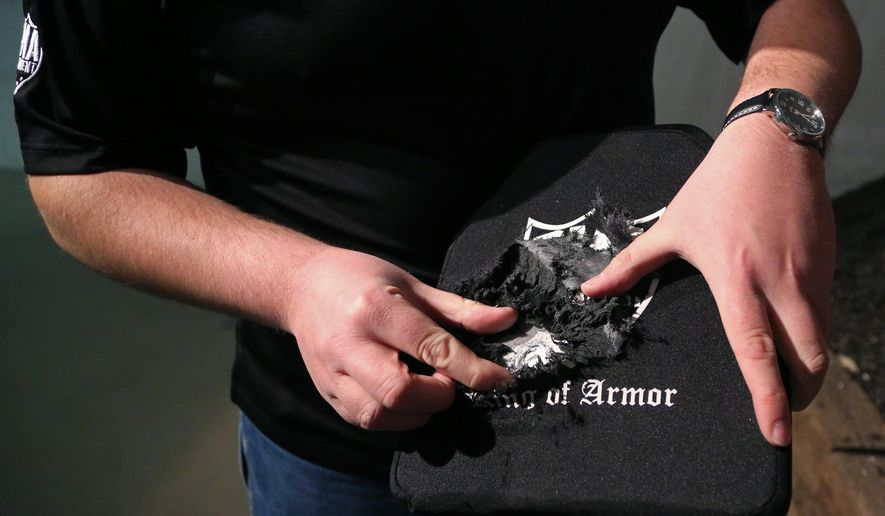 ADVANCE FOR USE SUNDAY, JAN. 22 - In this Wednesday, Jan. 11, 2017 photo, Blake Waldrop, CEO of RMA Armament  in Centerville, Iowa, holds a body armor plate created by RMA after its been fired at to show how the ceramic front of the plate works. (Kelsey Kremer/The Des Moines Register via AP )