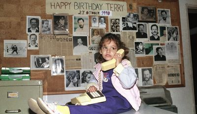"""FILE - In this Dec. 24, 1990, file photo, Sulome Anderson, daughter of Associated Press journalist Terry Anderson, the longest-held hostage in Lebanon, plays with her father's telephone at his office in Beirut. Sulome said a multi-year retracing of her father's harrowing ordeal repaired their tattered relationship. Sulome describes the quest in """"The Hostage's Daughter,"""" a recently published book. Her effort to research the 1985 kidnapping of Terry in Beirut, Lebanon, eventually brought her face-to-face with one of his captors. Ultimately, it led her to see eye-to-eye with her father again.  (AP Photo/Ahmed Azakir, File)"""