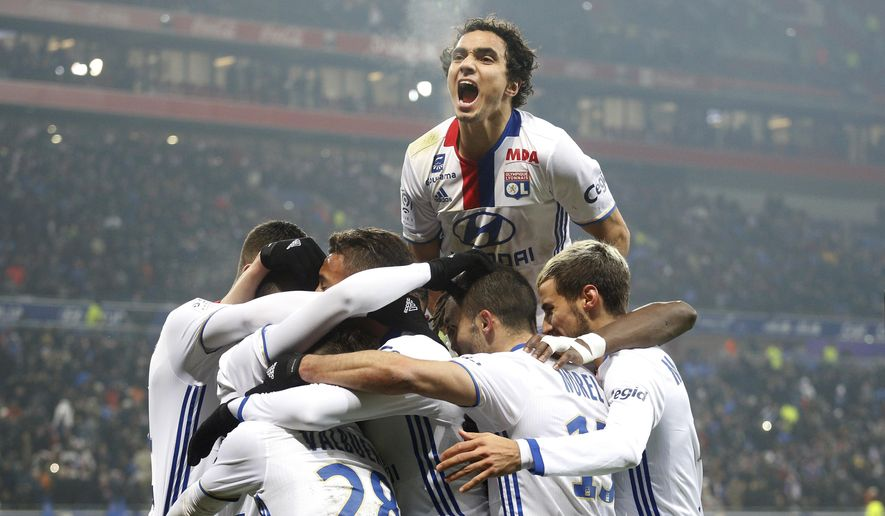 Lyon's Rafael Pereira Da Silva celebrates with teammates after Lacazette scored a goal against Marseille during their French League One soccer match in Decines, near Lyon, central France, Sunday, Jan. 22, 2017. (AP Photo/Laurent Cipriani)