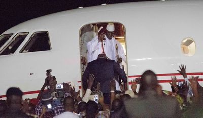 Gambia's defeated leader Yahya Jammeh waves to supporters as he departs at Banjul airport Saturday Jan. 21, 2017. Jammeh announced early Saturday he has decided to relinquish power, after hours of last-ditch talks with regional leaders and the threat by a regional military force to make him leave. (AP Photo/Jerome Delay)