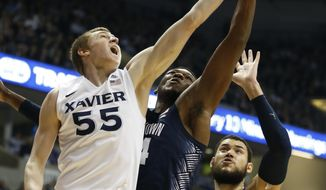Xavier guard J.P. Macura (55) shoots against Georgetown's Marcus Derrickson, center, and Bradley Hayes (42) during the second half of an NCAA college basketball game, Sunday, Jan. 22, 2017, in Cincinnati. (AP Photo/Gary Landers)