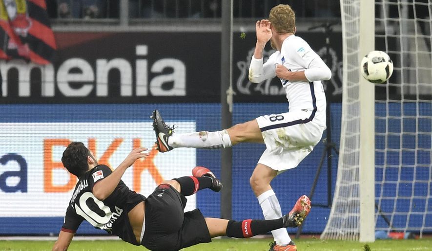 Leverkusen's Hakan Calhanoglu, left, scores his second goal during the German Bundesliga soccer match between Bayer Leverkusen and Hertha BSC Berlin in Leverkusen, Germany, Sunday, Jan. 22, 2017. (AP Photo/Martin Meissner)