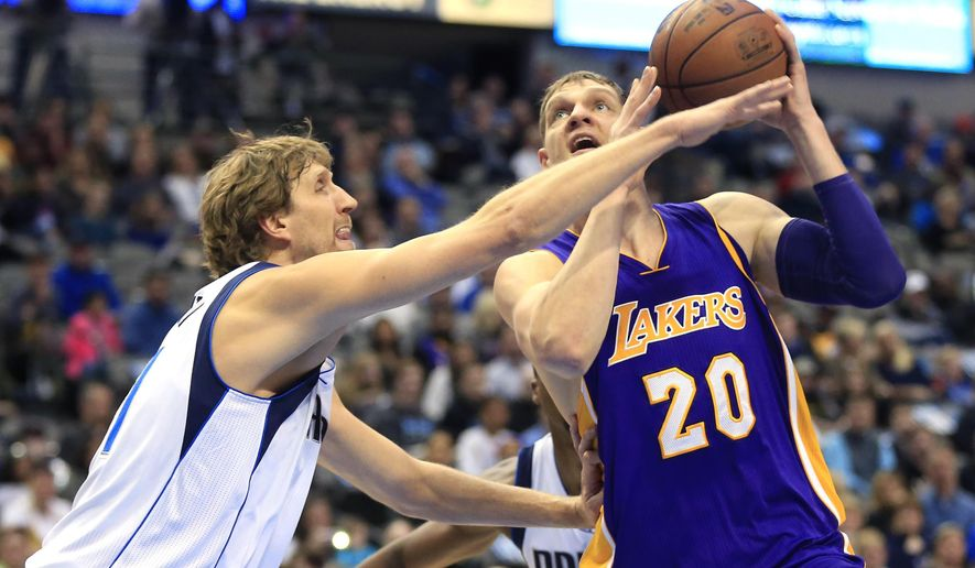 Dallas Mavericks forward Dirk Nowitzki (41) tries to stop Los Angeles Lakers center Tarik Black (28) from driving inside during the first half of an NBA basketball game, Sunday, Jan. 22, 2017, in Dallas. (AP Photo/Ron Jenkins)