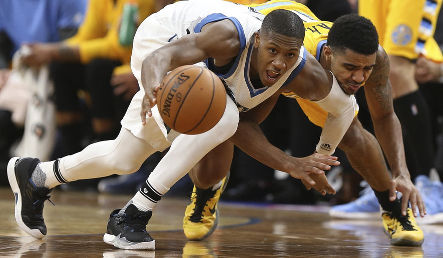 Minnesota Timberwolves guard Kris Dunn (3) tries to grab a lose ball against Denver Nuggets guard Gary Harris, right, in the first half of an NBA basketball game, Sunday, Jan. 22, 2017, in Minneapolis. (AP Photo/Stacy Bengs)