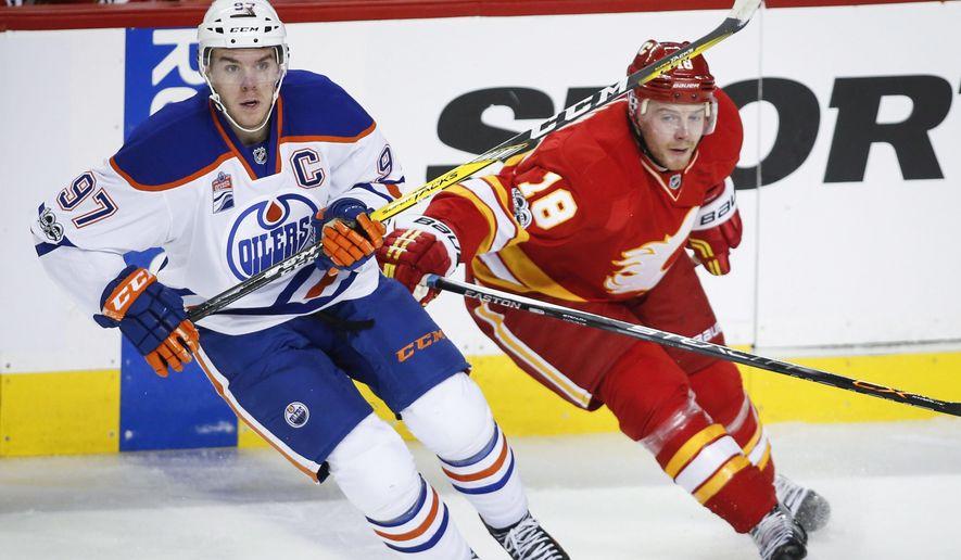 Edmonton Oilers' Connor McDavid, left, tangles with Calgary Flames' Matt Stajan during the second period of an NHL hockey game Saturday, Jan. 21, 2017, in Calgary, Alberta. (Jeff McIntosh/The Canadian Press via AP)
