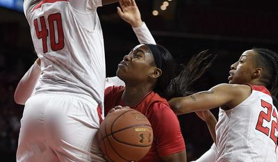 Maryland's Kaila Charles, center looks to shoot as Rutgers' Victoria Harris, left, and Kandiss Barber defend during the first half of an NCAA college basketball game, Sunday, Jan. 22, 2017, in College Park, Md. (AP Photo/Gail Burton)